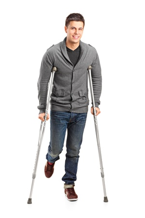 Full length portrait of an injured young man on crutches isolated on white background photo