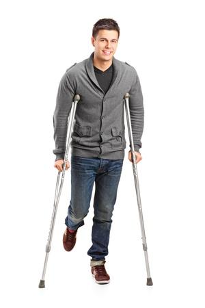 In voller Länge Portrait eines verletzten jungen Mann auf Krücken isoliert auf weißem Hintergrund