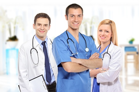 apparatus: Medical team consisting of three smiling doctors inside a hospital