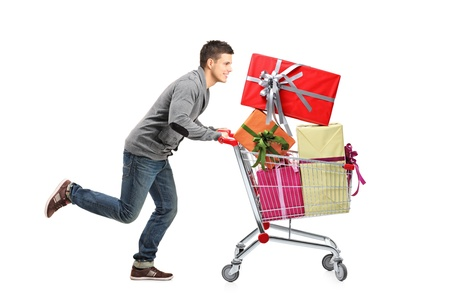 happy shopper: Young man running and pushing a shopping cart with gifts isolated on white background