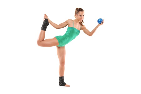 A female athlete working out with a ball isolated on white background photo