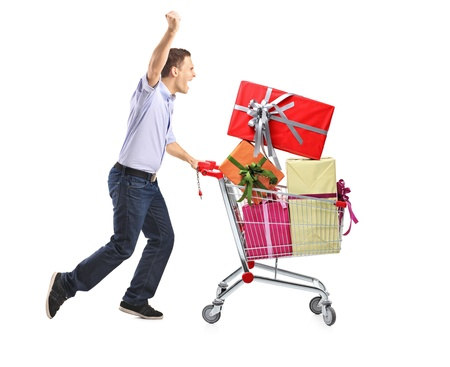 Euphoric male pushing a shopping cart full with gifts isolated on white background photo