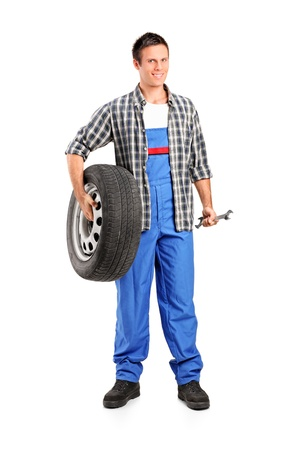 mecanico: Retrato de cuerpo entero de un mec�nico de la celebraci�n de una rueda de repuesto y la celebraci�n de una llave sobre fondo blanco