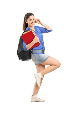 Full length portrait of a smiling school girl holding books and talking on a phone isolated on white background photo