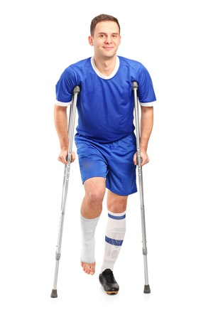 crutch: Full length portrait of an injured soccer football player on crutches isolated against white background