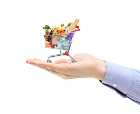 Hand holding a shopping cart full with groceries isolated on white background photo