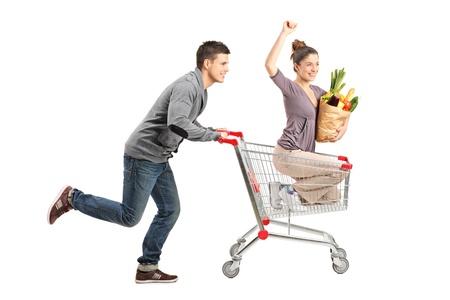 bolsa de pan: Persona que empuja a una mujer feliz en un carrito de la compra con el útil de bolsas de papel con los alimentos aislados sobre fondo blanco