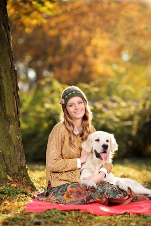 Smiling young woman hugging a labrador retreiver dog out in the park photo