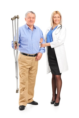 Full length portrait of a female doctor or nurse holding a senior patient with crutches isolated on white background photo