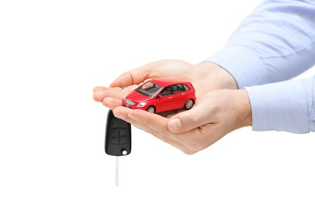 Male hands holding a car and keys isolated on white background photo