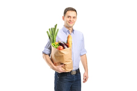 A man holding a shopping bag full of food isolated on white background photo