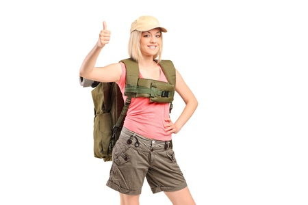 A smiling female hiker with backpack giving thumb up isolated on white background photo
