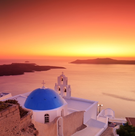 Blue dome Church St. Spirou in Firostefani on the island of Santorini Greece, at sunset photo