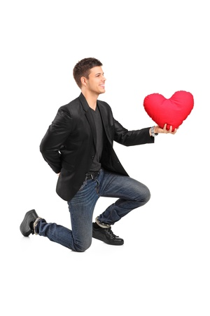 A romantic man on his knees practicing a proposal and holding a red heart shaped pillow isolated on white background photo