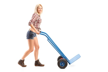 Full length portrait of a female manual worker pushing an empty handtruck isolated on white background photo