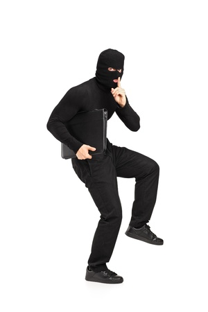 Full length portrait of a man in robbery mask holding a briefcase with finger on the lips gesturing silence isolated on white background photo