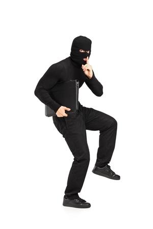 bandidas: Retrato de cuerpo entero de un hombre en la m�scara de un robo con un malet�n con el dedo en los labios un gesto silencio aislado sobre fondo blanco