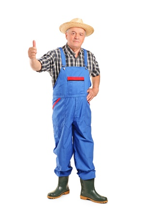 Full length portrait of a senior smiling farmer giving a thumb up isolated on white background photo