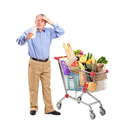 groceries: Retrato de cuerpo entero de un shock alto mirando recibo de la tienda junto a un carrito de compras aisladas sobre fondo blanco Foto de archivo