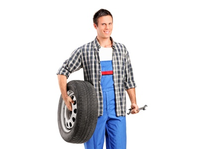 A mechanic holding a spare tire and a wrench isolated on white background Stock Photo - 11759046