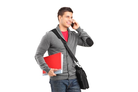 A smiling school boy holding books and talking on a phone isolated on white background photo