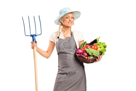 A female farmer holding a pitchfork and basket with vegetables isolated against white background photo