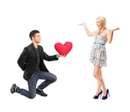 A romantic man on his knees holding a red heart shaped pillow and an excited blond woman isolated on white background photo