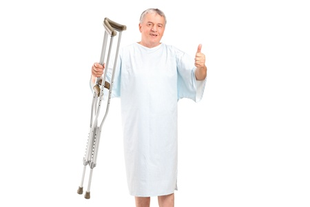 A senior patient holding crutches and giving thumb up isolated on white background Stock Photo - 11958261