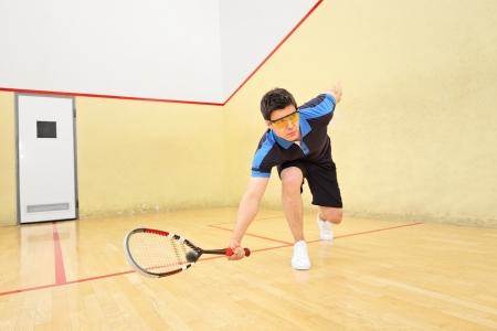 Un jeune joueur de squash hiting une balle dans un terrain de squash