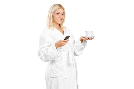 Full length portrait of a young woman in bathrobe holding a coffee cup and mobile phone isolated on white backgroundA young woman in bathrobe holding a coffee cup and mobile phone isolated on white background photo