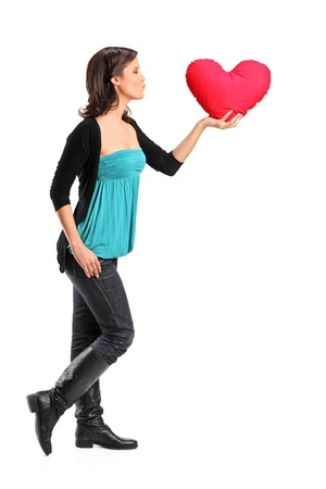 Full length portrait of a female holding a red heart shaped pillow isolated on white background Stock Photo - 11958273