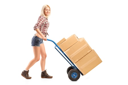 handtruck: Full length portrait of a female manual worker pushing a handtruck with boxes on it isolated on white background