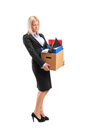 unemployed dismissed: Full length portrait of a fired businesswoman in a suit carrying a box of personal items isolated on white background Stock Photo