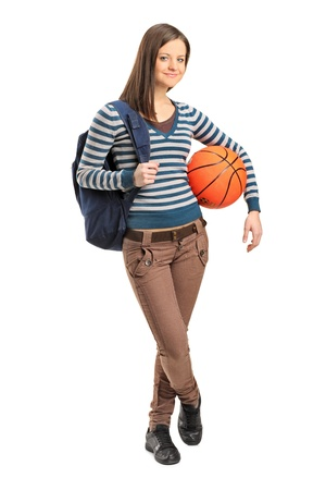 baloncesto chica: Retrato de cuerpo entero de una niña de la escuela joven que sostiene una pelota de baloncesto aislados sobre fondo blanco Foto de archivo