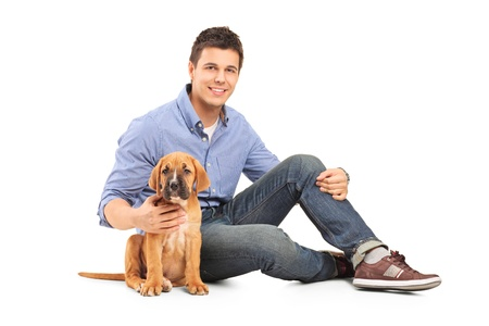 Young man with a cane corso puppy isolated on white background photo