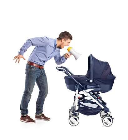 A mad father yelling to his baby laid down in a baby carriage isolated on white background photo