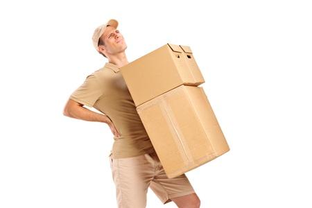 dolor de espalda: Un repartidor de padecer dolor de espalda mientras que las cajas que llevan aisladas sobre fondo blanco Foto de archivo