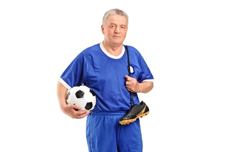 A senior wearing a sport wear holding a soccer shoes and football isolated on white background Stock Photo - 11961970