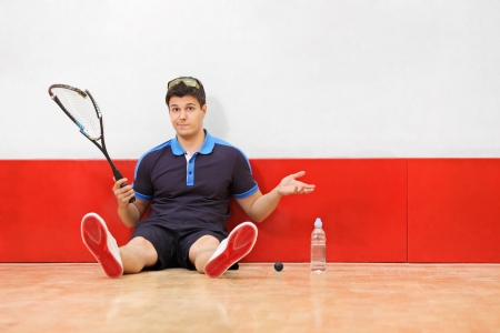 sports clothing: A young disappointed squash player holding a broken racket in a squash court Stock Photo