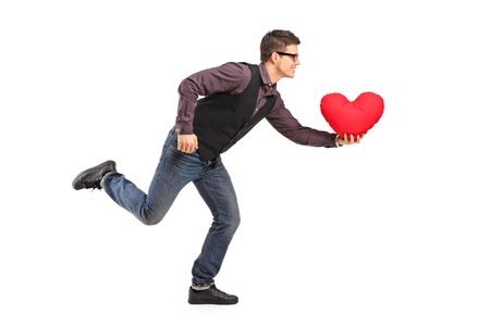 A young man running with a red heart shaped pillow in his hand isolated on white background photo