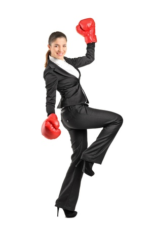Full length portrait of a beautiful business woman wearing boxing gloves isolated on white background photo