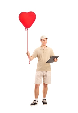 Full length portrait of a delivery boy delivering a red heart shaped balloon isolated on white background photo