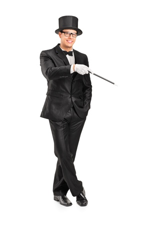 Full length portrait of a magician holding a magic wand posing isolated on white background photo