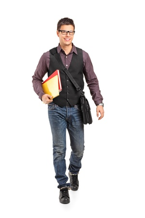 person walking: Full length portrait of a smiling school boy walking and holding books isolated on white background