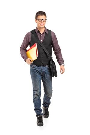 niño con mochila: Retrato de cuerpo entero de un niño de la escuela caminando y sonriendo la celebración de libros aislados en el fondo blanco Foto de archivo