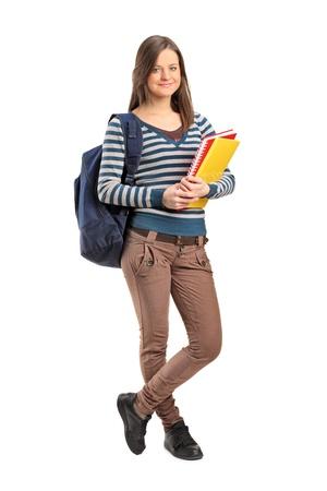 adolescencia: Retrato de cuerpo entero de una niña de la escuela sonriendo posando con sus libros sobre fondo blanco