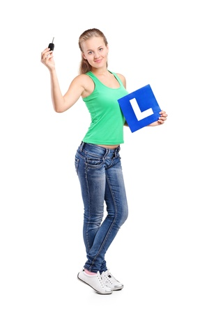 learner: Full length portrait of a smiling teenager holding a L plate and car key isolated on white background