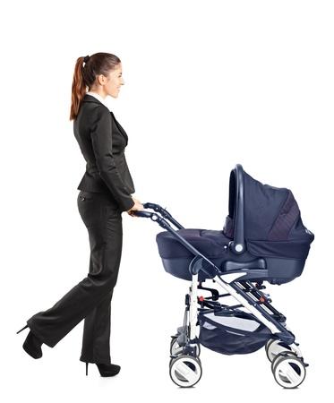 ni�o empujando: Retrato de cuerpo entero de una joven empresaria empujando un cochecito de beb� sobre fondo blanco Foto de archivo