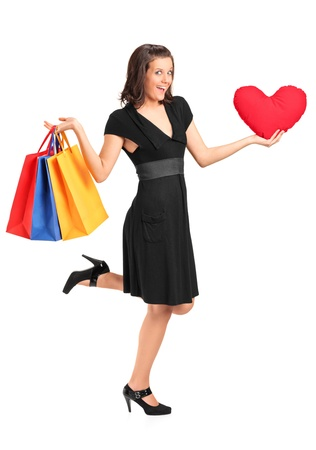 Full length portrait of a smiling female holding a red heart shaped pillow and shopping bags isolated on white Stock Photo - 11961928