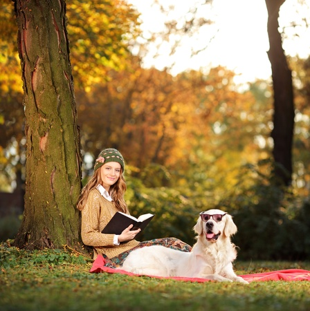 Smiling young woman relaxing in a city park with her labrador retriever dog photo